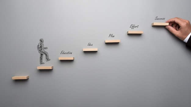 途中で教育、アイデア、計画、努力という言葉で成功に向けて階段を上るシルエットのビジネスマン。灰色の背景の上。