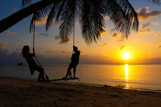 Silhouetted couple in love walks on the beach during sunset. riding on a swing tied to a palm tree and watching the sun go down into the ocean