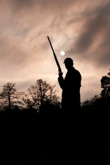 Silhouetted hunter with gun