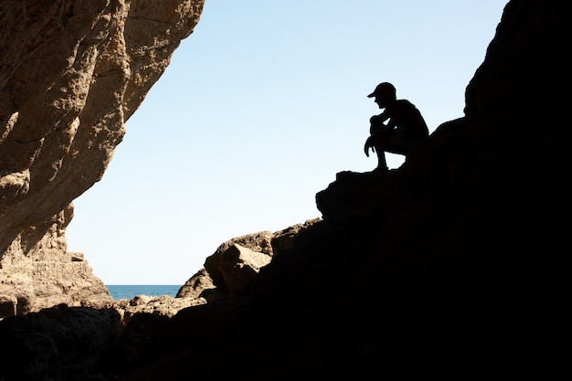 Silhouetted men on a rock in the backlight