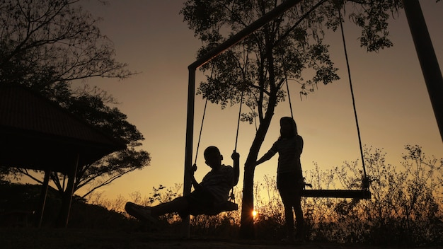 Silhouetted young mother with boy enjoying beautiful sunny day, swinging background