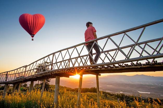 Silhouetted азиатского человека стоя на бамбуковом мосте с краснокалильным воздушным шаром в форме сердца над заходом солнца.