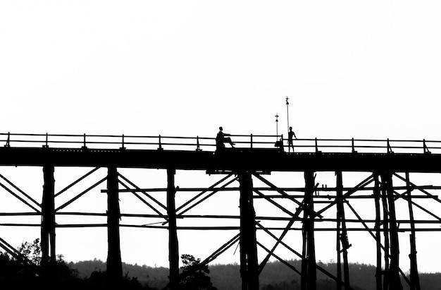 Silhouetted человек, сидящий на стуле в мост на закате, сангкла, провинция канчанабури, таиланд