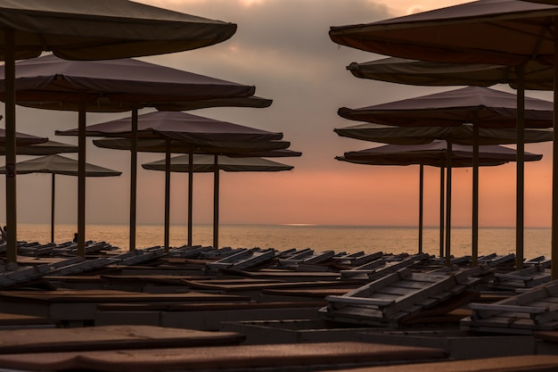 Silhouettes of beach loungers and umbrellas on an empty beach in the evening