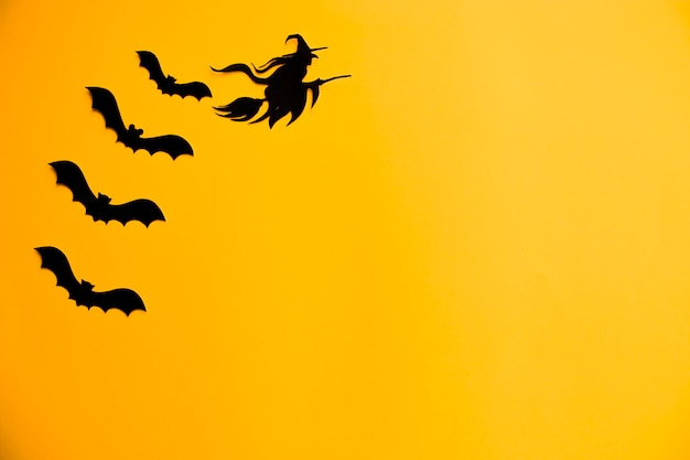 Silhouettes of black bats and witch on broom made of paper on orange halloween background.