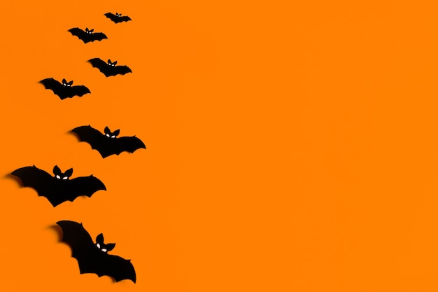 Silhouettes of black paper bats on an orange background for halloween