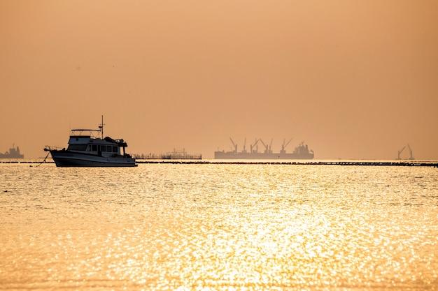海と夕日のシルエットのボート