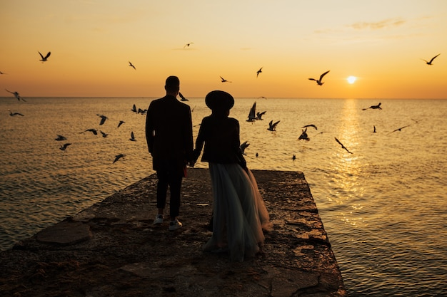 Silhouettes of bride and groom holding hands while walking on beach against sun during amazing sunset and flying seagulls on surface.