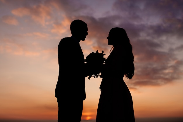 Silhouettes of the bride and groom, the newlyweds look at each other holding a wedding bouquet in their hands. wedding photography concept.