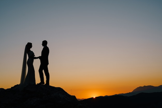 Silhouettes of the bride and groom stand on the mountain against the background of the sunset