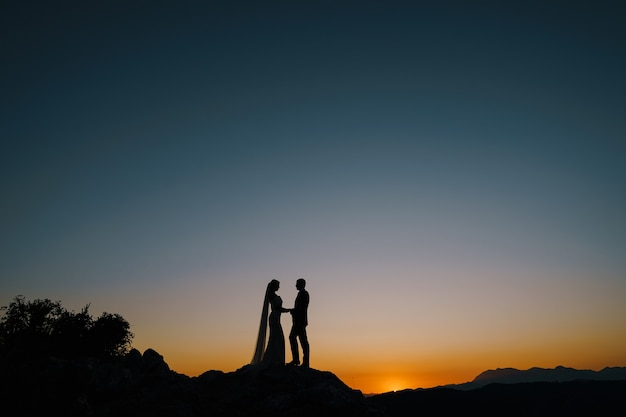 Silhouettes of the bride and groom stand on the mountain on the sunset
