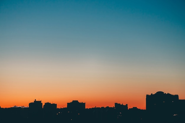 Silhouettes of buildings on background of sunset orange sky