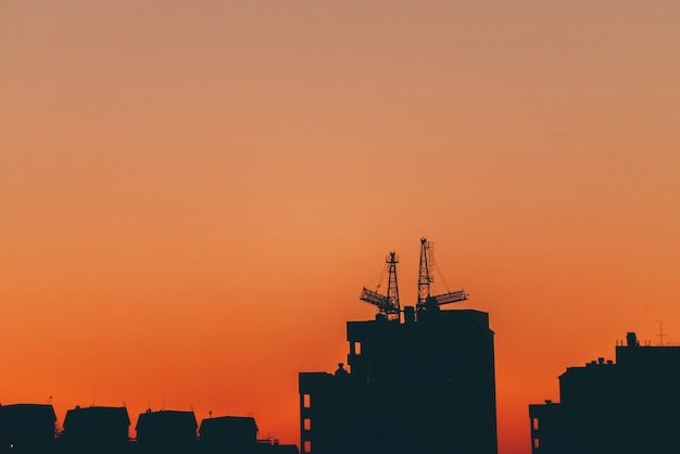 Silhouettes of buildings on orange background of sunset sky