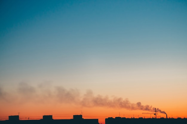 Silhouettes of buildings and smoke on background of sunset orange sky