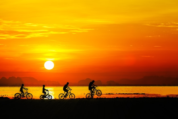 Silhouettes of childrens on bicycle against sunset sky at the beach.