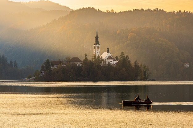 Silhouettes of a couple floating on a boat near the bled island at beautiful sunset light