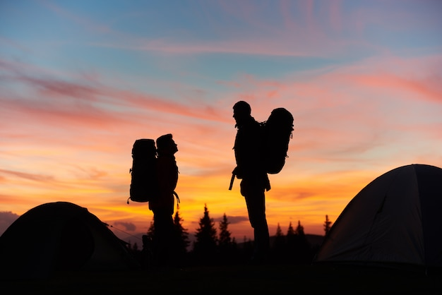 Silhouettes of a couple of hikers with backpacks standing on top of a rock enjoying dusky landscape