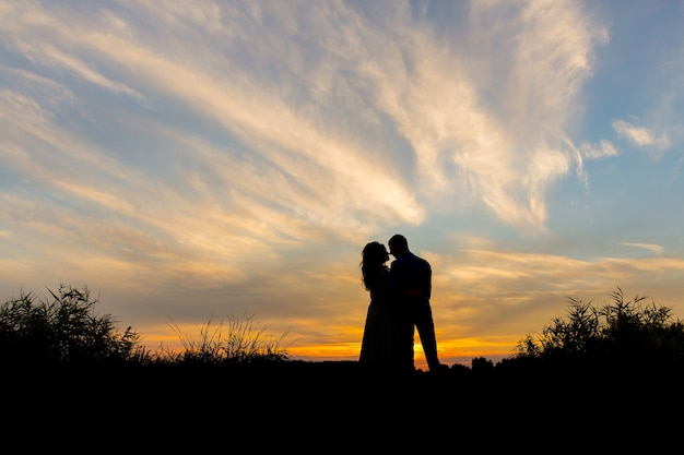 Silhouettes of a couple in love against the backdrop of sunset