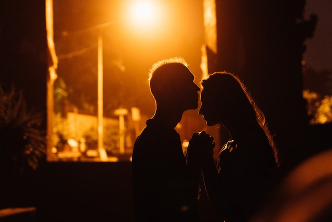 Silhouettes of couple in love in night city