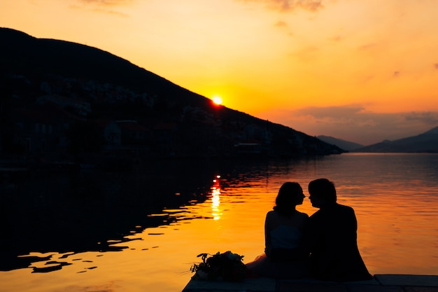 Silhouettes of couple sit on the pier above the water against the backdrop of mountains and sunset