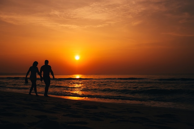 Silhouettes of a couple walking along the beach by the sea