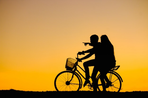 Silhouettes couples and bicycle on sunset sky