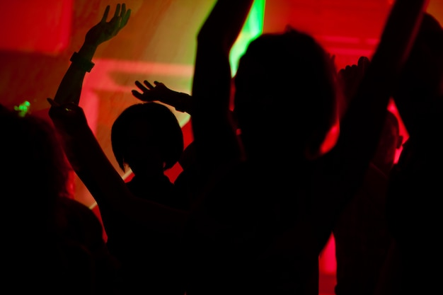Silhouettes of dancing people having a celebration in a disco club