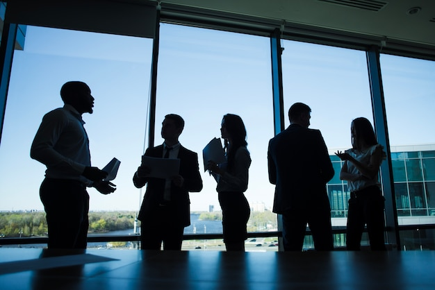 Silhouettes of discussing business people
