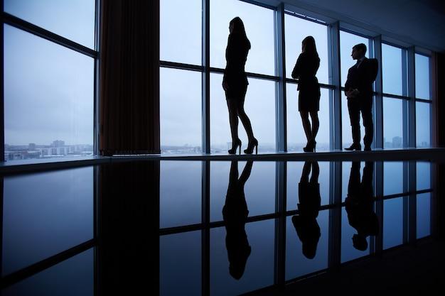 Sagome di dipendenti guardando attraverso le finestre