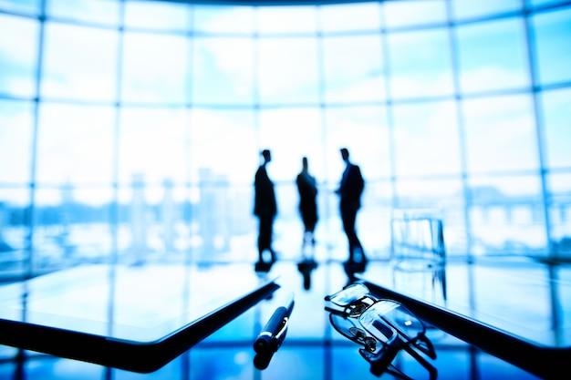 Silhouettes of executives negotiating background