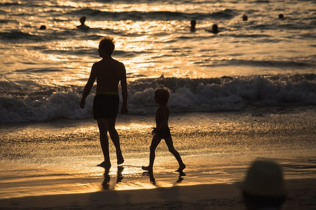Silhouettes of father and son on sunset beach sea