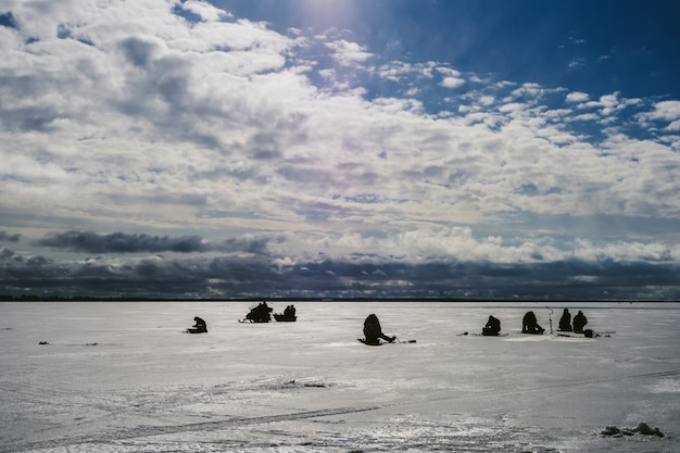 Silhouettes of fishermen fishing and snowmobile in winter on the ice