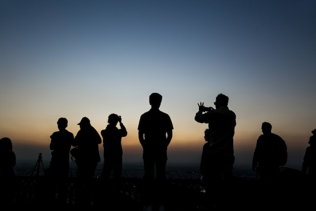 Silhouettes group of people taking pictures at sunset in nahagarh fort jaipur.