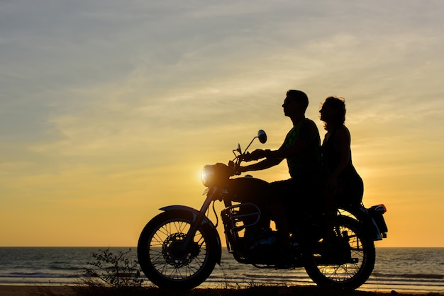 Silhouettes of guy and girl on a motorcycle on sunset background.