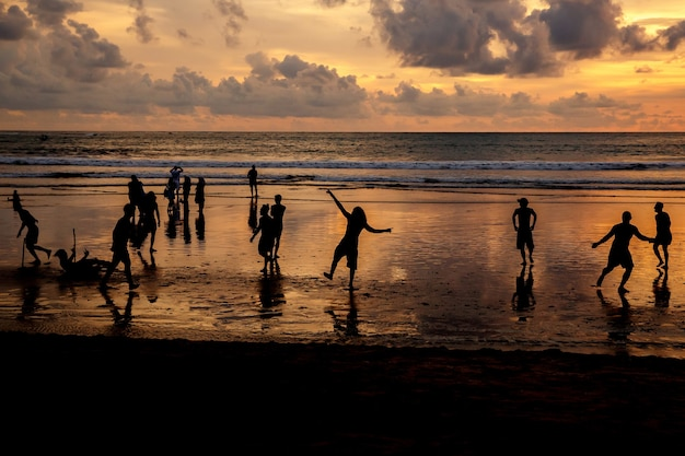 Silhouettes of guys who play soccer at sunset on the ocean beach.