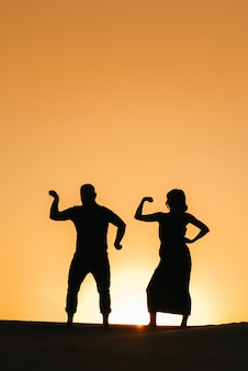 Silhouettes of a happy young couple guy and woman