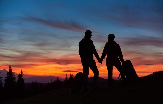 Silhouettes of hiking couple enjoying stunning sunset on top of the mountain holding hands