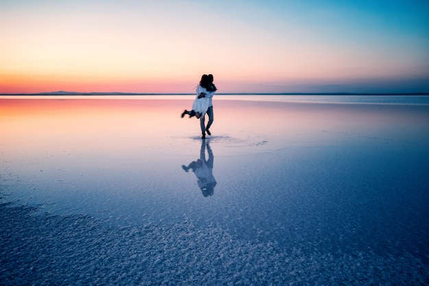 Silhouettes of hugging happy lovers in middle of shallow water