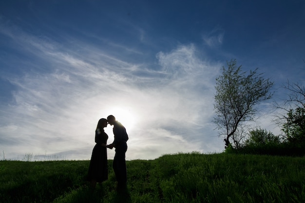 Silhouettes of love couples on the nature in summer evening.young man and woman tenderly embracing in the sunset.