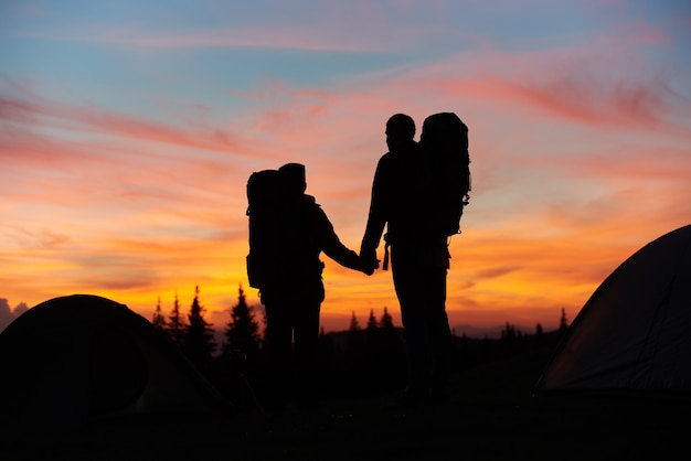 Silhouettes of a loving couple holding hands standing on top of the mountain while hiking