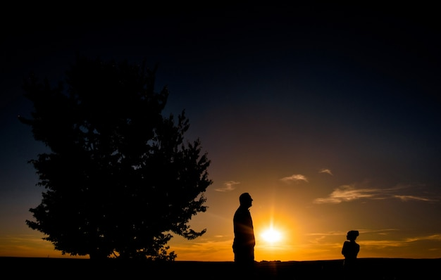 Silhouettes of man and girl standing on a field before a sunset