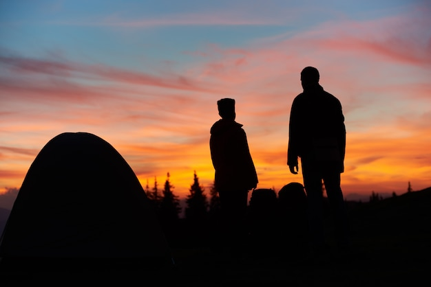 Silhouettes of a man and woman standing near their tent on top of a mountain stunning sunset