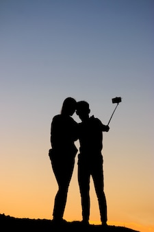 Silhouettes man and woman taking selfie with smartphone on sunset sky