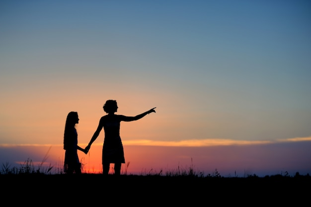 Silhouettes of mother and daughter against the sunset sky