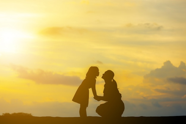 Silhouettes of mother and daughter playing at sunset evening