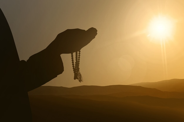 Silhouettes of muslim people praying to god
