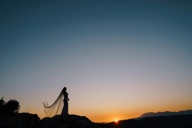 Силуэты невесты в развевающейся вуали, стоящей на горе и смотрящей на закат