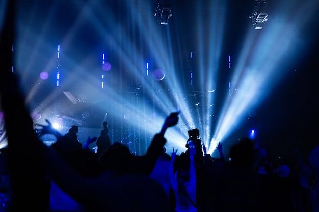무대 위의 밝고 화려한 광선을 배경으로 콘서트 관중과 카메라맨의 실루엣. 오퍼레이터가 있는 카메라는 높은 플랫폼에 있습니다.