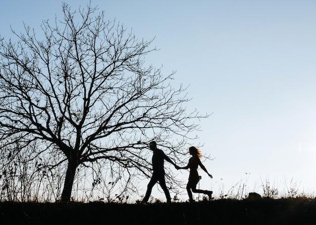 木々の間を歩いて、屋外で男性と女性のカップルのシルエット。