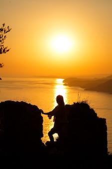 海と夕日を背景に女の子のシルエット